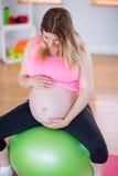 Femme enceinte touchant son ventre sur la boule d'exercice Photographie stock libre de droits