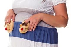 Femme enceinte trouant les bootees de la chéri à son ventre Photographie stock