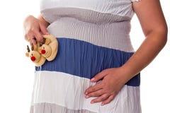 Femme enceinte trouant les bootees de la chéri à son ventre Photos stock