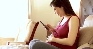 Femme enceinte utilisant un appli clips vidéos
