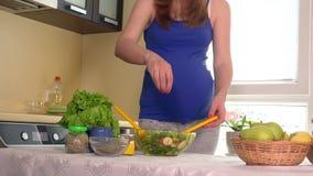 Femme enceinte verser le sel et mélanger la salade naturelle écologique de légumes dans le bol en verre clips vidéos