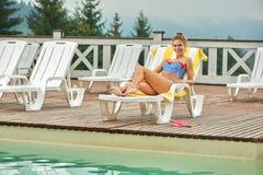 Femme enjoing ses vacances, se trouvant sur la chaise de plage près de la piscine images stock