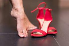 Femme enlevant les sandales rouges de talon haut photos stock