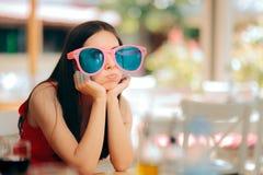 Femme ennuyée avec de grands verres drôles de partie n'ayant aucun amusement photo stock