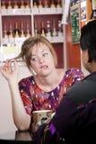 Femme ennuyée dans le café avec l'ami mâle Photo stock