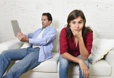 Femme ennuyée et frustrée ignoré tandis que mari ou ami d'intoxiqué d'Internet employant la mise en réseau numérique de comprimé Photographie stock libre de droits