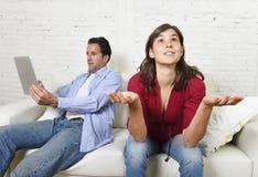 Femme ennuyée et frustrée ignoré tandis que mari ou ami d'intoxiqué d'Internet employant la mise en réseau numérique de comprimé Photos stock