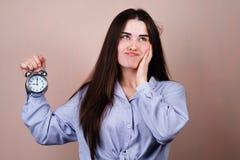 Femme ennuyée et soumise à une contrainte avec le réveil photographie stock