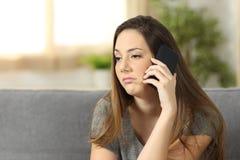 Femme ennuyée pendant un appel téléphonique image libre de droits