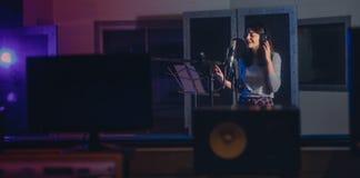 Femme enregistrant une chanson dans le studio de musique image stock