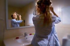 Femme enroulant son cheveu photo stock