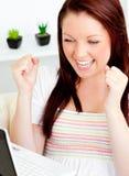 Femme enthousiaste à l'aide de son ordinateur portatif se reposant sur un sofa Image libre de droits