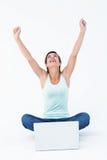 Femme enthousiaste avec l'ordinateur portable soulevant ses bras Image stock