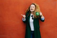 Femme enthousiaste avec la veste de port bouclée de cheveux blonds tenant la tasse de café verte soulevant son pouce lui montrant photo libre de droits