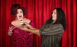 Femme enthousiaste avec le petit gâteau et l'homme nerveux Photographie stock libre de droits