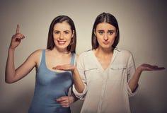 Femme enthousiaste ayant la solution, et fille naïve ennuyée et contrariée Photo libre de droits