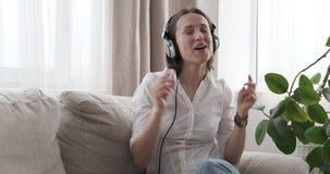 Femme enthousiaste chantant tout en écoutant la musique dans des écouteurs clips vidéos