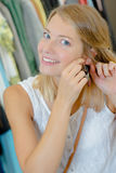 Femme enthousiaste essayant sur de nouvelles boucles d'oreille à l'intérieur Photos stock