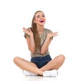 Femme enthousiaste et heureuse s'asseyant sur le plancher Photo libre de droits