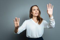 Femme enthousiaste gaie se tenant sur le fond gris Photos stock