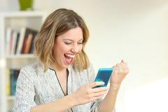 Femme enthousiaste lisant le contenu futé de téléphone images stock