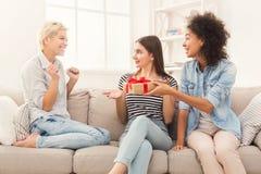 Femme enthousiaste obtenant le cadeau de ses amis Images libres de droits