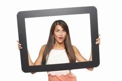 Femme enthousiaste regardant par le cadre de comprimé Images stock