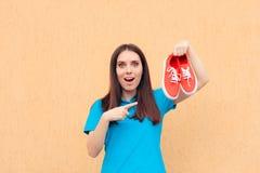 Femme enthousiaste tenant une paire de chaussures rouges de sport image libre de droits