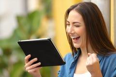 Femme enthousiaste vérifiant des nouvelles sur le comprimé dans la rue photo stock