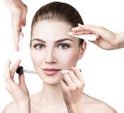 Femme entourée par des dispositifs de cosmétiques Images libres de droits