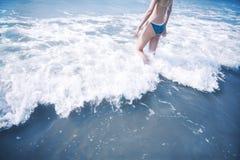 Femme entrant dans des vagues à la plage photo libre de droits