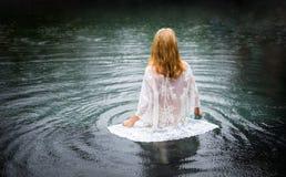 Femme entrant dans l'eau photo stock