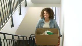 Femme entrant dans la nouvelle boîte de transport à la maison en haut banque de vidéos