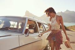 Femme entrant dans la voiture pour le voyage par la route avec des amis Photo stock
