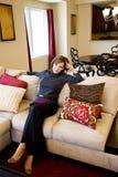 Femme entre deux âges détendant sur le sofa de salle de séjour images stock