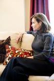 Femme entre deux âges détendant sur le sofa de salle de séjour image libre de droits