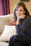 Femme entre deux âges détendant sur le sofa de salle de séjour photos stock