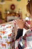 Femme enveloppant des cadeaux de Noël à la maison avec des lumières de bokeh photos stock