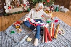 Femme enveloppant des cadeaux de Noël photos stock