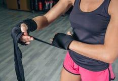 Femme enveloppant des mains avec des bandages avant la boxe Photos libres de droits