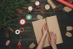 Femme enveloppant le cadeau de Noël Photos stock