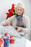 Femme enveloppant le cadeau de Noël Photographie stock libre de droits