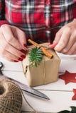 Femme enveloppant le cadeau naturel de Noël Images stock