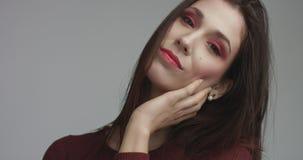 Femme espagnole de beauté dans la robe rouge avec le maquillage rouge d'oeil de vivd regardant l'appareil-photo Photographie stock libre de droits