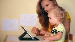 Femme espiègle avec la fille de fille d'enfant en bas âge à l'aide de la tablette clips vidéos