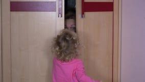 Femme espiègle se cachant de l'enfant de fille dans le cabinet de garde-robe à la maison banque de vidéos