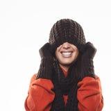 Femme espiègle se cachant sous un chapeau d'hiver Photographie stock libre de droits