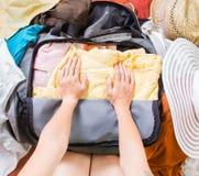 Femme essayant d'emballer des vêtements dans un sac Photo libre de droits