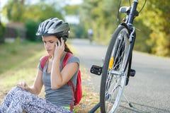 Femme essayant de fixer le problème de vélo appelle l'ami Photo stock
