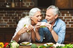 Femme essayant de manger le sandwich à maris photographie stock libre de droits